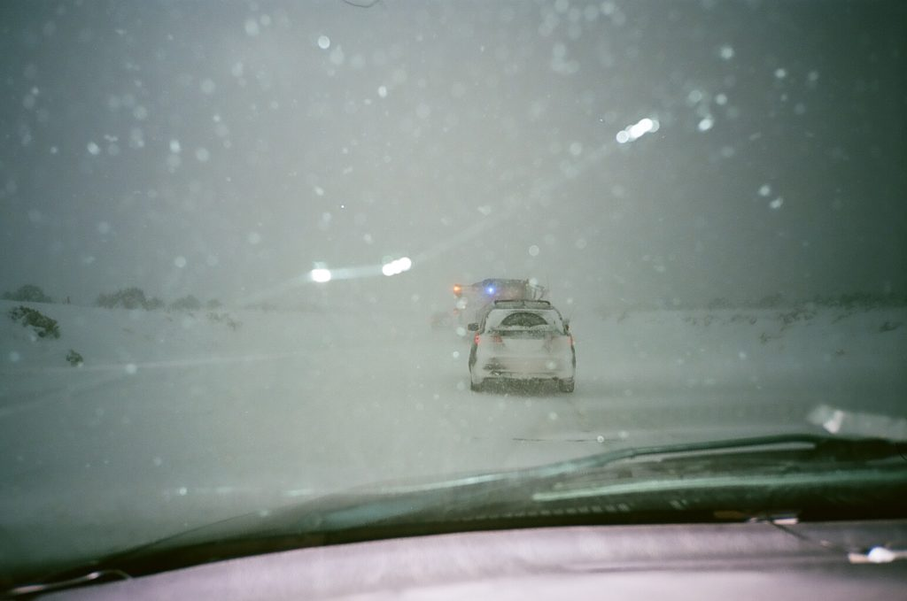 Photograph out of a cracked vehicle window of a white-out blizzard.