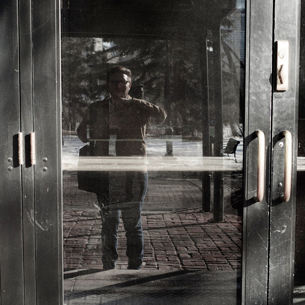 Self-photo of the author as reflected in a glass door on a fall day,