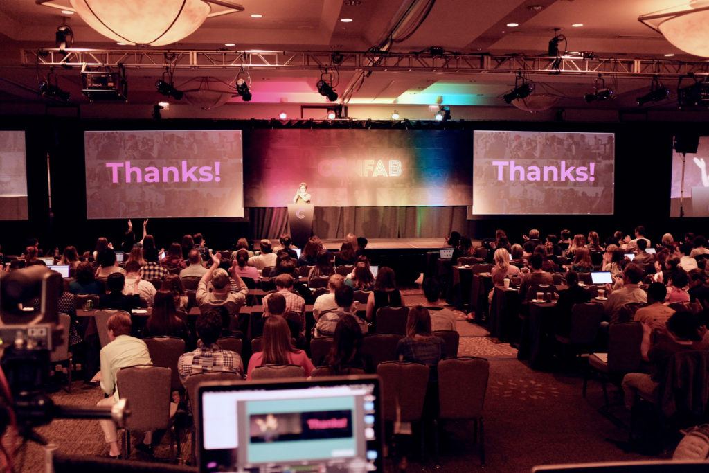 Wide shot of the crowd at Confab 2019, with 'Thanks!' displayed on the screens.