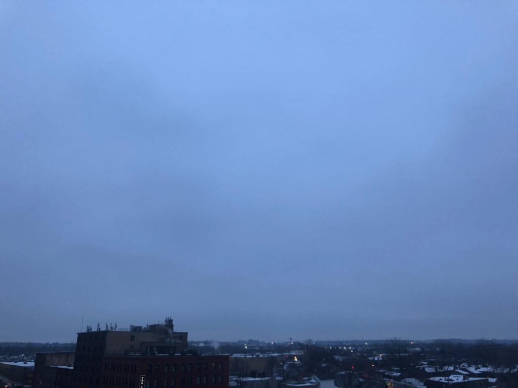 Hazy dark blue morning light over a city skyline.