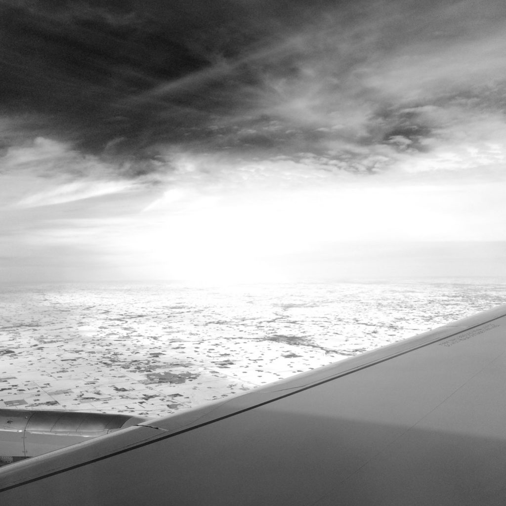 Photograph of a partial airplane wing and open sky, as photographed out of the plane window.