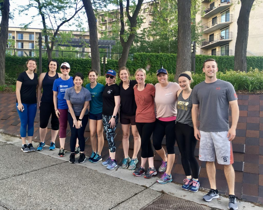 11 people in exercise clothes posing before a run.