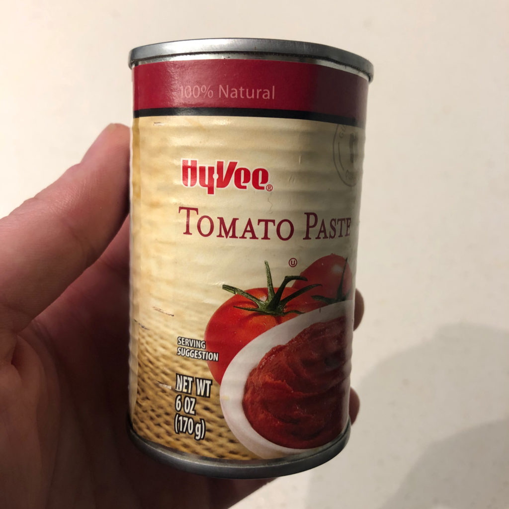 Photo of a hand holding a can of HyVee brand tomato paste.