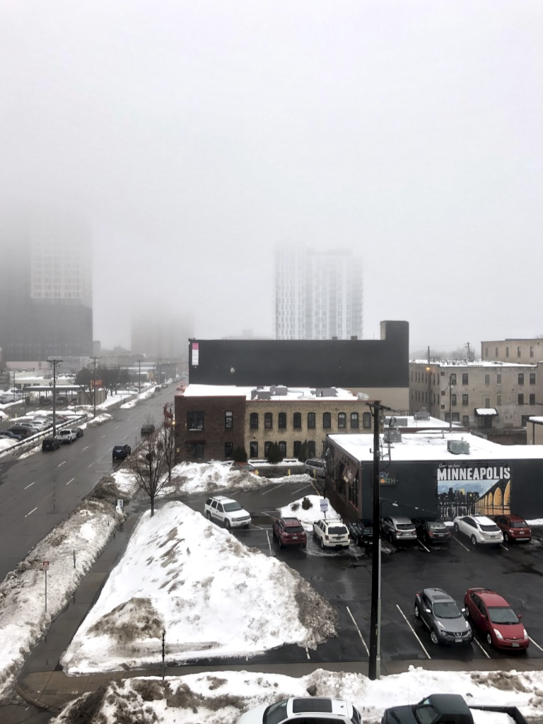 Photograph of a foggy, snowy scene over downtown Minneapolis buildings.